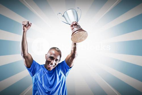Composite image of portrait of happy sportsman cheering while holding trophy
