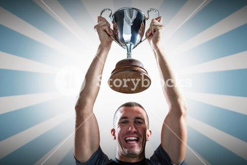 Composite image of portrait of successful rugby player holding trophy