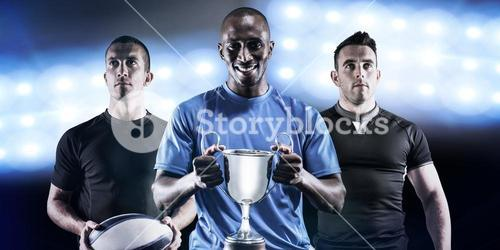 Composite image of portrait of happy athlete holding trophy