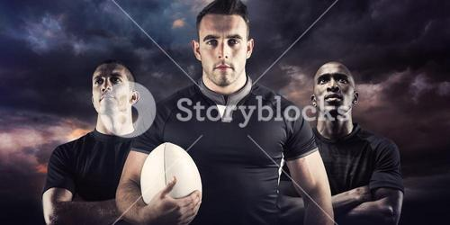 Composite image of tough rugby player holding ball