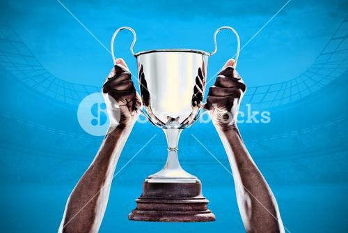 Composite image of cropped hand of athlete holding trophy