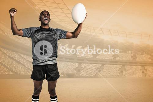 Composite image of cheerful sportsman with clenched fist holding rugby ball