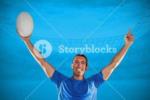Composite image of portrait of rugby player in blue jersey holding ball with arms raised