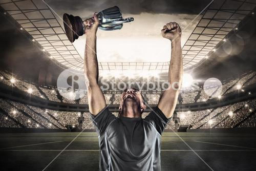 Composite image of happy rugby player holding trophy