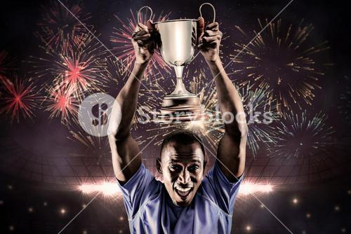 Composite image of portrait of happy athlete cheering while holding trophy