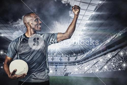 Composite image of sportsman with clenched fist holding rugby ball after victory