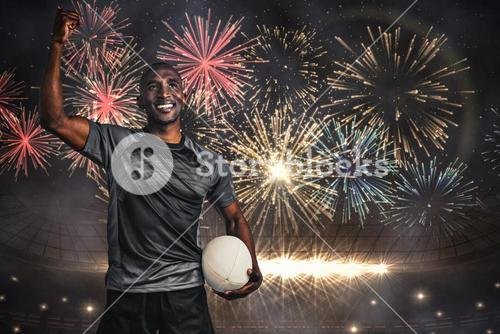Composite image of happy sportsman with clenched fist holding rugby ball