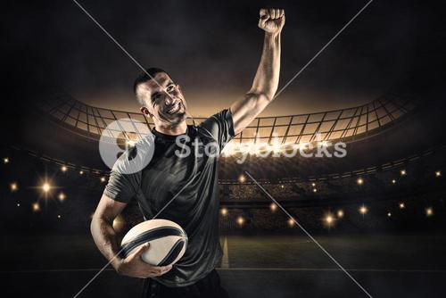 Composite image of happy rugby player punching the air