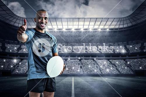 Composite image of portrait of confident rugby player smiling and showing thumbs up