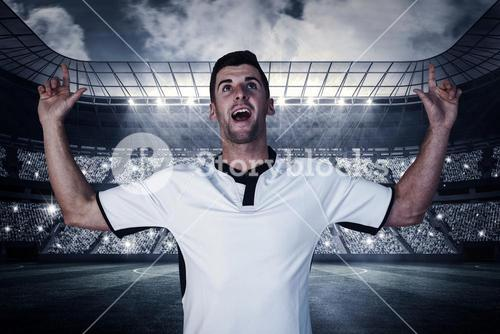 Composite image of surprised rugby player pointing up