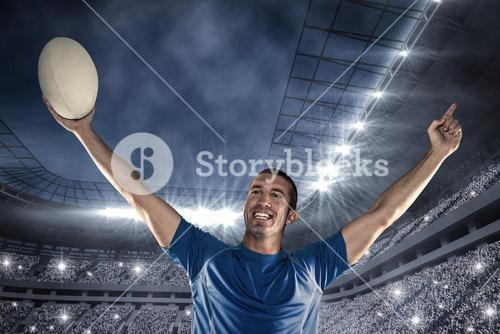 Composite image of happy rugby player in blue jersey holding ball with arms raised