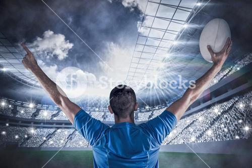 Composite image of rear view of rugby player holding ball with arms raised