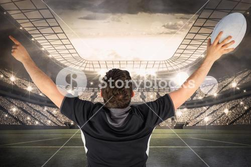 Composite image of back turned rugby player gesturing victory