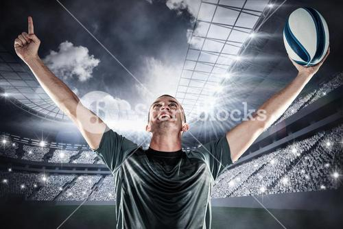 Composite image of successful rugby player holding ball with arms raised