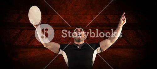 Composite image of rugby player cheering with the ball