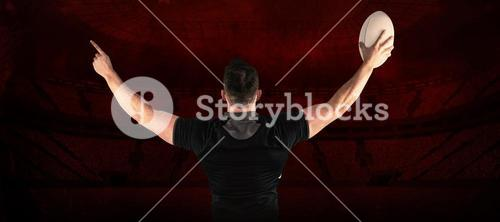 Composite image of rugby player celebrating with the ball