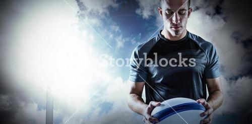 Composite image of serious rugby player holding ball
