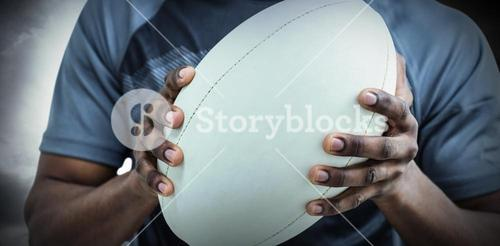 Composite image of mid section of sportsman holding rugby ball
