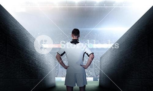 Composite image of rear view of a rugby player with hands on waist