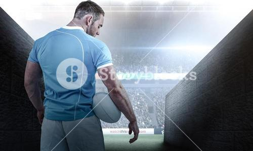 Composite image of rugby player standing with ball