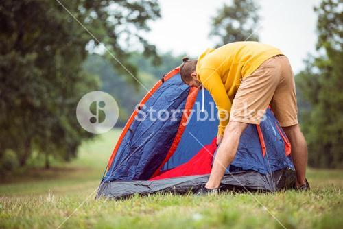 Handsome hipster pitching his tent