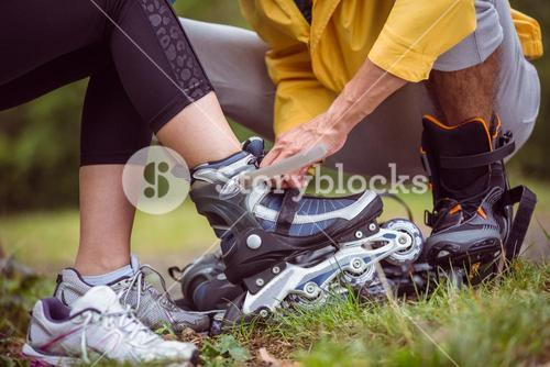 Happy couple putting on roller blades