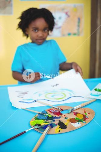 Happy kid painting on a sheet