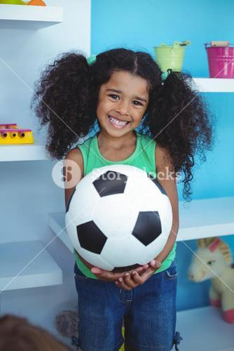 Small girl holding a soccer ball