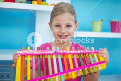 Smiling girl holding a xylophone