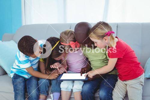 Happy kids using technology while sitting