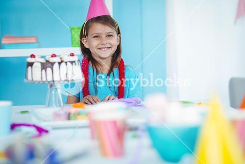 Smiling kid beside birthday cake