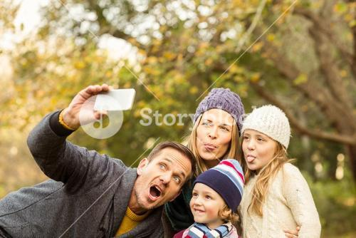 Smiling young family taking selfies