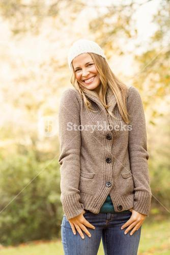Smiling pretty woman with hands in pocket