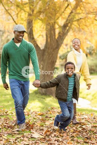 A little boy pulling his parents to walk more quickly