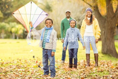 Young family playing with a kite