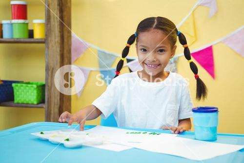Smiling girl who is finger painting