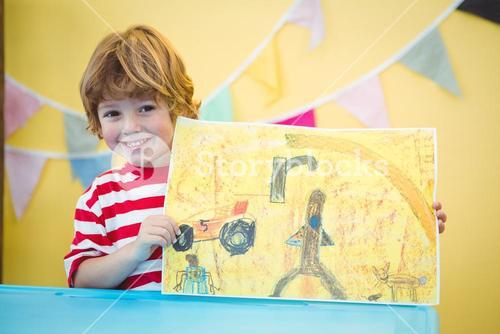 Smiling child holding up his finished painting