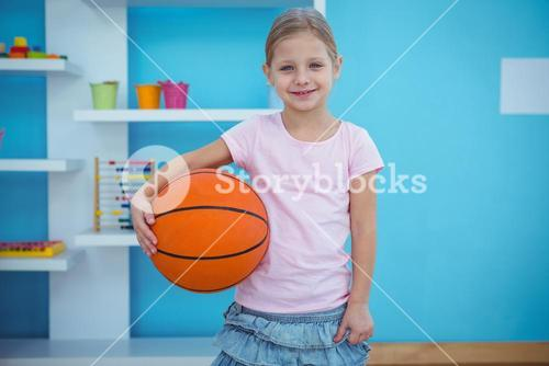 Cute girl holding basket ball