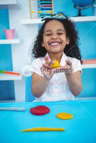Cute girl using modeling clay