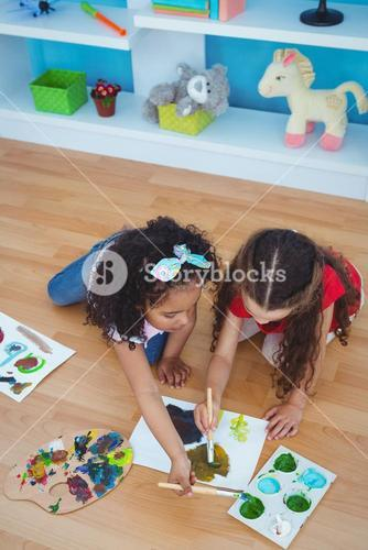 Cute girls painting laying on the floor