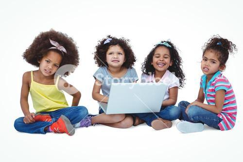 Cute girls sitting on the floor using laptop