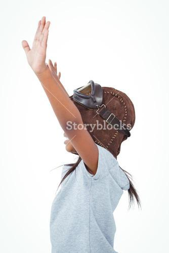Side view of girl with outstretched arms pretending to be pilot