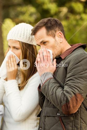 Sick couple blowing their noses