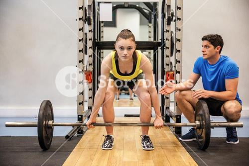 Woman lifting barbell with trainer spotting her