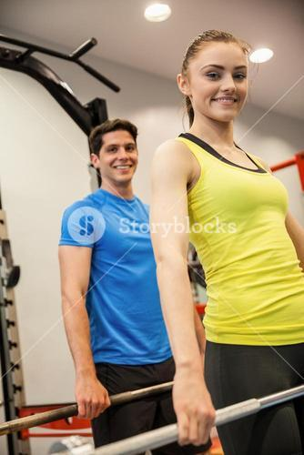 Man and woman lifting barbells together