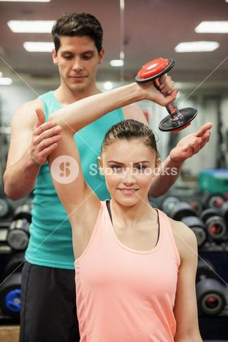 Trainer helping client work out