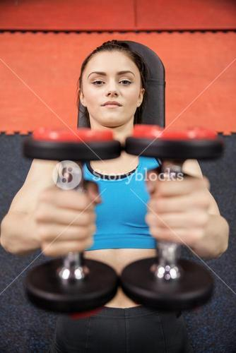 Smiling woman lifting dumbbells while lying down
