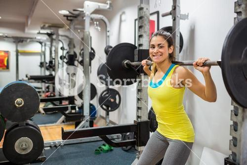 Determined woman lifting a barbell