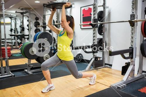 Determined woman doing lunges while holding a weight overhead