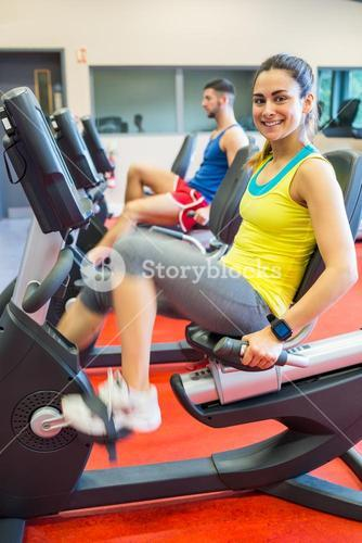 Man and woman using exercise machines